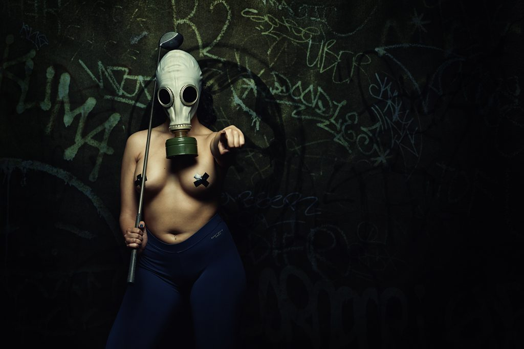 Girl with gas mask and golf club