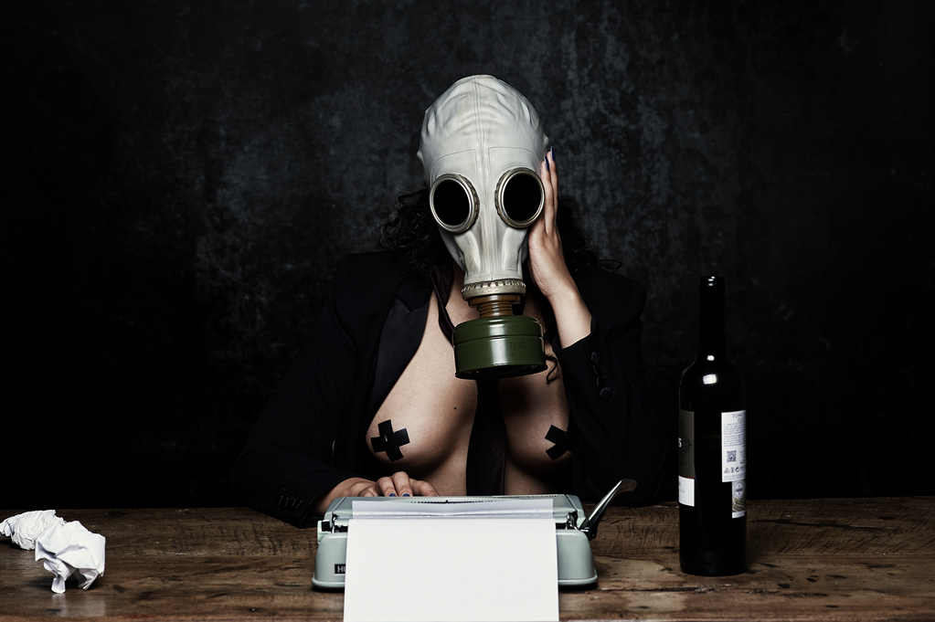 Girl with gas mask, writing machine and a bottle of wine